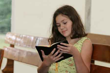 image of a 9 year old girl reading the Bible
