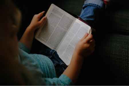 image of a teenager reading the Bible